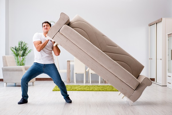 Young man moving furniture at home for local move