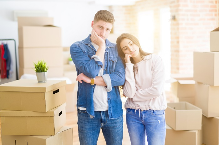 Beautiful young couple moving to a new house thinking looking tired and bored with depression problems with crossed arms.